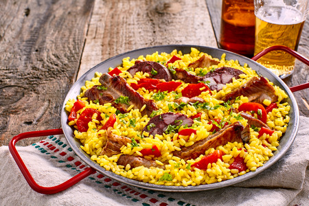 homo: Wholesome Spanish al homo paella with black pudding and grilled spare ribs served on a bed of savory saffron rice with herbs and red bell peppers