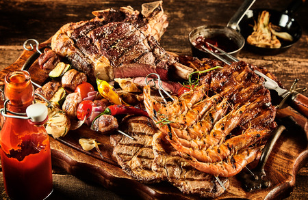 Catered barbecue beef, shrimp and skewered vegetables served on table with oil, ketchup and seasonings