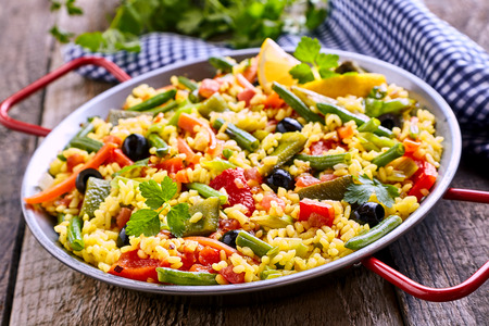 Close Up of Colorful and Fresh Vegetarian Paella Spanish Rice Dish Served in Pan with Red Handles and Linen Napkin on Rustic Wooden Table