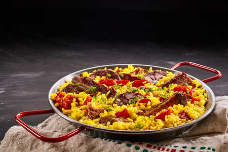 homo: Rustic metal dish of delicious traditional Spanish paella al homo with black pudding and spare ribs on yellow saffron rice with red sweet peppers, with copy space
