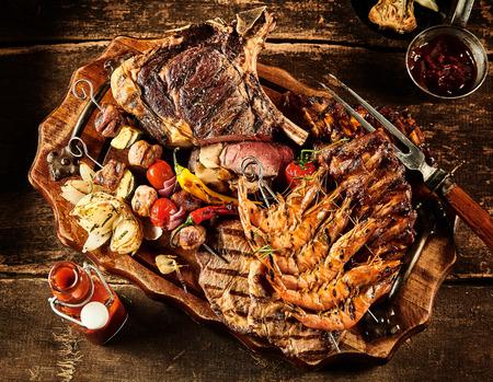 Verscheidenheid van barbecue rundvlees, garnalen en diverse groenten geserveerd op tafel met olie, ketchup en kruiden Stockfoto
