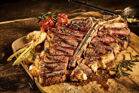 porterhouse: Medium rare cooked large porterhouse steak in front of roasted garlic and tomato placed on cutting board over old wooden table
