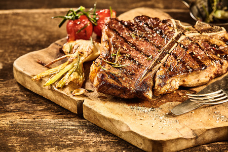 Cooked large t-bone steak and roasted garlic and tomato placed on cutting board over old splintering table