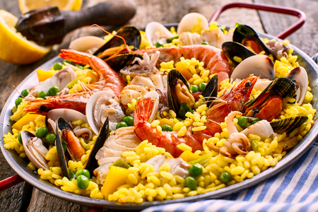 Close Up of Colorful Spanish Seafood Paella Dish with Langostina and Shellfish Served in Shallow Pan with Red Handles on Rustic Wooden Table with Fresh Lemon Garnish in Background