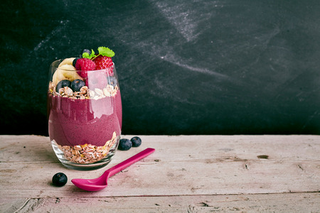 acai berry: Deliciously sweet acai fruit dessert with pieces of banana, strawberry and blueberry with oats next to spoon on wooden table with copy space