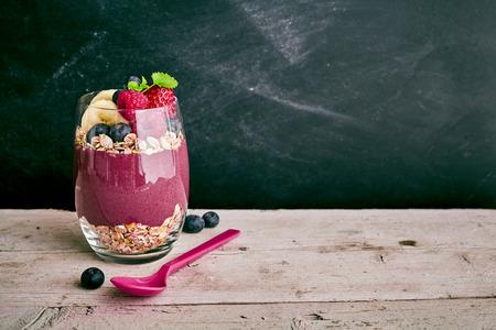 Heerlijk zoete acai fruit dessert met stukjes banaan, aardbeien en bosbessen met haver naast lepel op een houten tafel met een kopie ruimte
