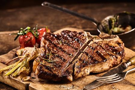 準備の大規模な t ボーン ステーキ焼きトマトに囲まれ、フォークとナイフはまな板の上の横にある調味料を添えて