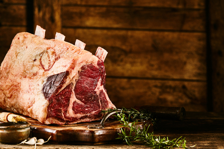 Close up view on raw cote de boeuf beef rib portion with rosemary over wooden plate and rustic background