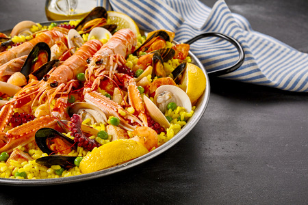 conceptional: Paella Valencia with fresh langoustines and assorted seafood and shellfish served on yellow saffron rice garnished with slices of fresh lemon, close up view Stock Photo