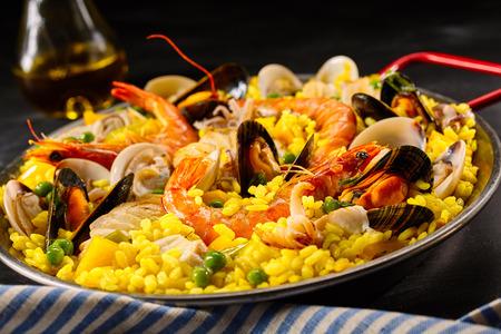 Paella a la margarita met schelpdieren waaronder roze garnalen, mosselen en mosselen op saffraan rijst met erwten voor een lekkere vis eten, close-up bekijken Stockfoto