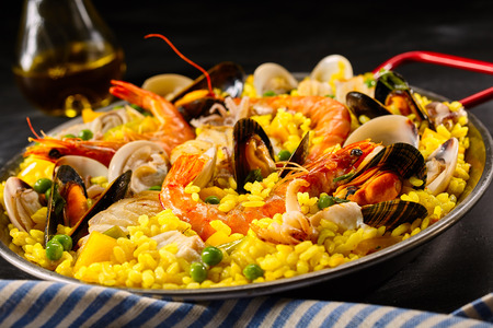 conceptional: Paella a la margarita with shellfish including pink prawns, clams and mussels on saffron rice with peas for a delicious seafood meal, close up view Stock Photo