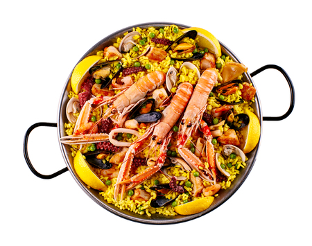 prepared dish: First person perspective view of three large shrimp cooked in pan full of rice, clams and lemon wedges on isolated background