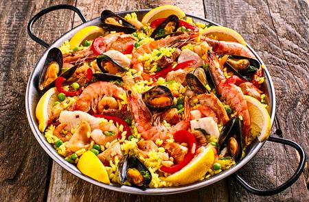 High Angle Sluit omhoog van kleurrijke Seafood Spaanse Paella Rice Schotel met garnalen en mosselen schelpdieren gegarneerd met verse citroen en geserveerd in een pan met groene linnen servet op rustieke houten tafel Stockfoto