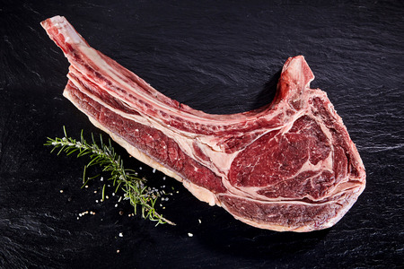 Einzelschnitt von rohem Tomahawk Rindfleisch mit Rosmarin und Salz auf schwarzem Stein Hintergrund Lizenzfreie Bilder