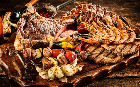 Various types of barbecued beef and seafood with roasted tomatoes and potatoes over wooden table background Stock Photo