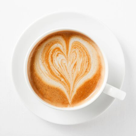 energising: Cup of cappuccino coffee with a heart shape in the milky foam on top viewed from above in a generic white cup and saucer on white