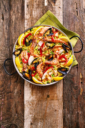 dish: High Angle View of Colorful Seafood Spanish Paella Rice Dish with Shrimp and Mussels Shellfish Garnished with Fresh Lemon and Served in Pan with Green Napkin on Rustic Wooden Table with Copy Space