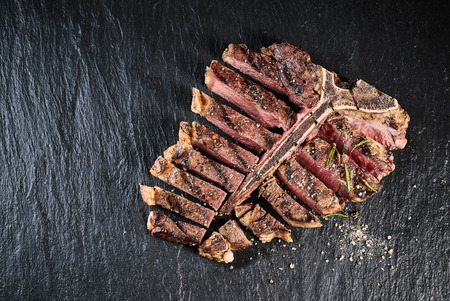 Gourmet grilled and sliced porterhouse steak seasoned with herbs and spices and served on a slate counter , high angle view