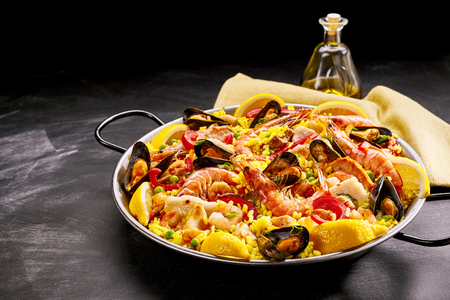 conceptional: Pan of gourmet paella with shrimp and mussels garnished with fresh lemon slices and served with oil or dressing in a decanter, with copy space