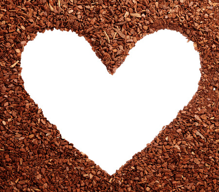bark mulch: Blank white heart symbol with copy space surrounded by pine bark mulch wood chips for romance or symbolic earth day greeting