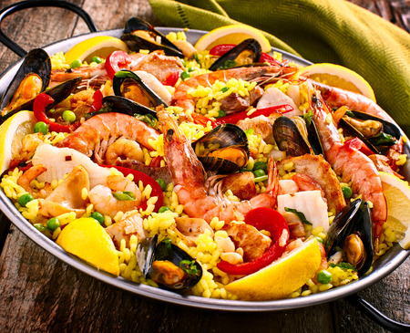 Close Up of Colorful Seafood Spanish Paella Rice Dish with Shrimp and Mussels Shellfish Garnished with Fresh Lemon and Served in Pan with Green Linen Napkin on Rustic Wooden Table