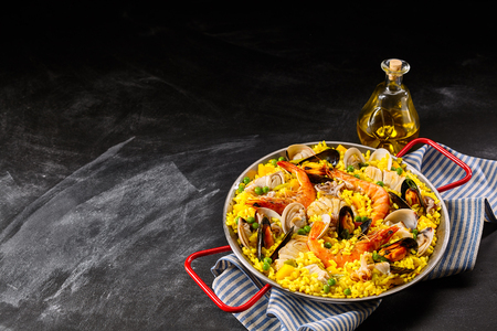 Homemade rice and seafood recipe in frying pan with red handles on blue and white cloth next to olive oil jar and copy space Фото со стока - 53511225