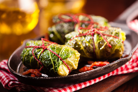 Close Up Still Life Detail of Fresh Appetizing Cabbage Rolls Tied with Red String and Served on Sizzling Cast Iron Pan with Red and White Gingham Towel on Rustic Wooden Table