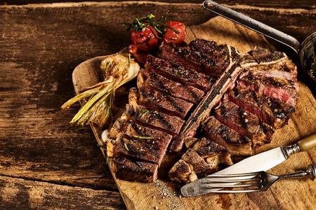 huesos: filete a la plancha grande en rodajas de carne en frente de ajo asado y tomate colocado en la tabla de cortar sobre la mesa de astillado de edad Foto de archivo