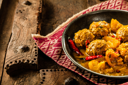 smothered: High Angle Close Up of Traditional Tajine Berber Dish of Meatballs Smothered in Spicy Yellow Curry Sauce with Hot Red Peppers and Served in Shallow Bowl on Cloth Napkin and Rustic Wooden Table