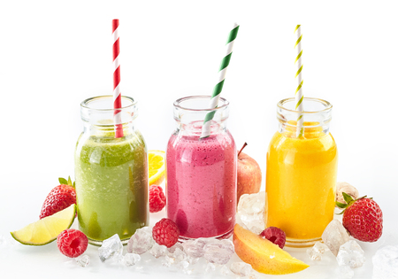 Drie gezonde smoothies met vers tropisch fruit, waaronder aardbeien, frambozen, sinaasappel, limoen, mango en appel, gekoeld op gemalen ijs en geserveerd in metselaarpotten Stockfoto