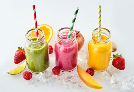 Row of apple, mango and strawberry smoothie beverages and matching straws surrounded by ice cubes and slices of fruit over gray background
