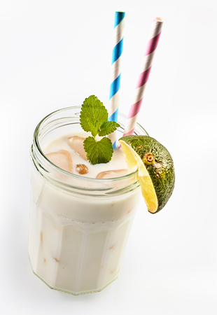 shaken: Single screw top glass jar as cup full of coco loco smoothie with lime and two straws over white background