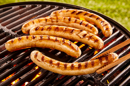 Pork sausages grilling on a portable BBQ with one sausage being turned in a pair of tongs on a summer picnic, close up of the grill, meat and fire