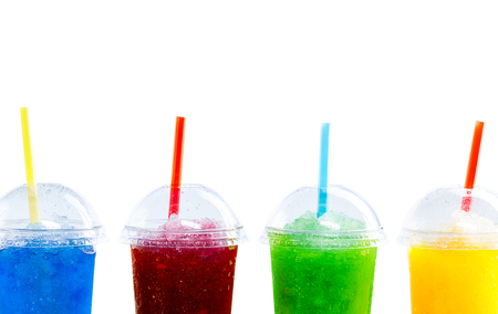 Close Up Still Life of Frozen Fruit Slush Granita Drinks in Plastic Take Away Cups with Lids and Drinking Straws Arranged in Row in front of White Background with Copy Space
