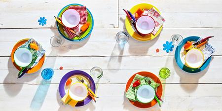 Bunte Picknick-Tisch Gedecke mit leeren bunten Teller und Schalen, Gläser und Blumen Abziehbilder für einen Spaß Sommer Grill, Draufsicht