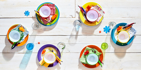 Colorful picnic table place settings with empty multicolored plates and bowls, glasses and flower decals for a fun summer barbecue, overhead view