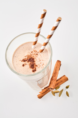 Top down view of delicious cinnamon smoothie garnished with cardomom beside herbs with two matching straws over white background Stok Fotoğraf