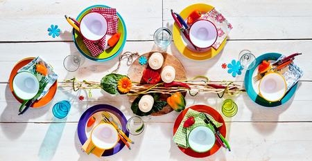 Colorful tavolo da picnic estate tropicale set con assortiti stoviglie e utensili da colori vivaci, con un centrotavola elegante con candele pronte fro cibo per essere servito, vista dall'alto Archivio Fotografico - 53744876