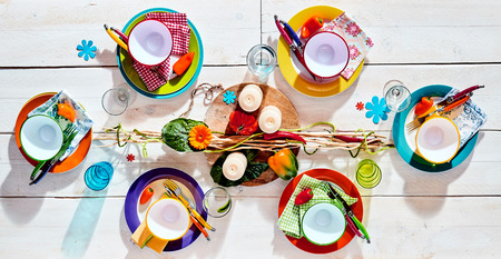 setting: Colorful tropical summer picnic table set with assorted brightly colored dinnerware and utensils with a stylish centerpiece with candles ready fro food to be served, overhead view