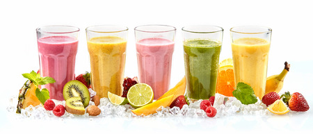 Row of five tropical fruit drinks in tall glasses next to strawberries raspberries and cut lime mango and kiwi standing in a bed of crushed ice Archivio Fotografico