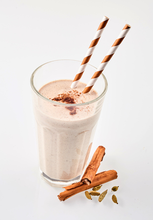 Cinnamon chai latte smoothie garnished with cardomom beside herbs with straws over white background