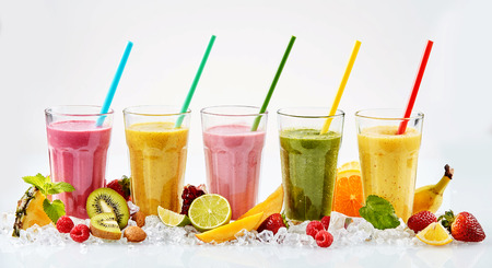 Five large glasses of red yellow pink and green tropical fruit smoothies with colorful straws standing in crushed ice beside cut fruit