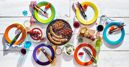 White picnic table set with colorful dinnerware and barbecued pork sausages, bread, and fresh fruit with drinks and decorative chili peppers, overhead view