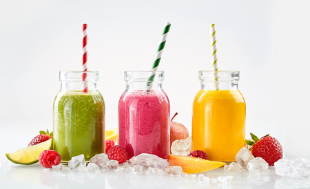 Row of apple, mango and strawberry smoothie beverages surrounded by ice cubes and various pieces of fruit over gray background