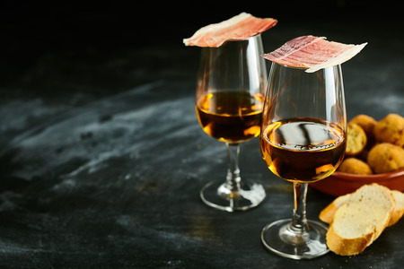 Het dienen van stijlvolle Spaanse tapas en aperitief met vers stokbrood, ham balancerend op de glazen sherry, en een kom van bacalao kroketten op een lei achtergrond met kopie ruimte