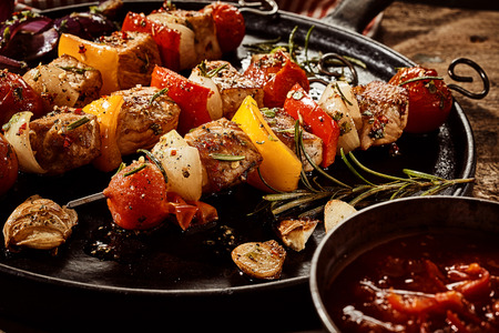 Colorful grilled skewers with meat and vegetables seasoned with herbs and fresh rosemary served with a spicy dipping sauce on a cast iron skillet