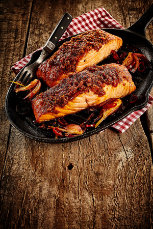 griddle: Spicy Mexican style baked salmon with sliced onions and fork in black cast iron griddle over napkin and rustic wooden table surface with copy space