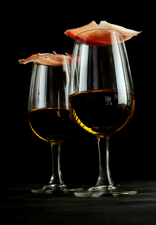 Gourmet ham balanced on glasses of Spanish sherry for an elegant tapas appetizer, low angle over a dark background