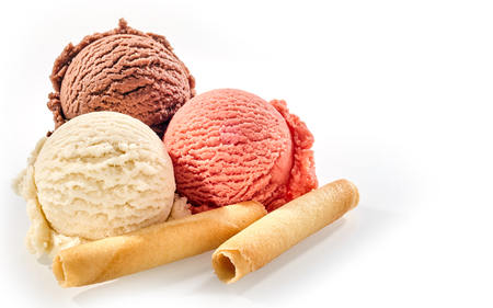 flavour: Three scoops of delicious homemade frozen italian dessert against a white background beside wafer rolls