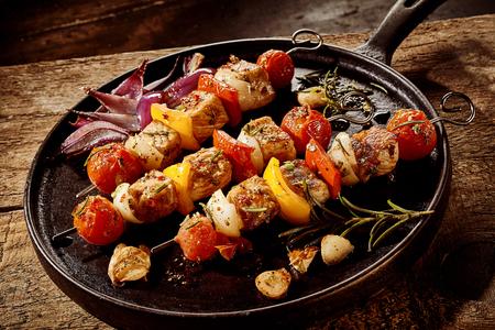 Drei leckere marinierte gegrillte Spieße mit Gemüse und Fleisch, gewürzt mit frischem Rosmarin und serviert auf einem alten gusseisernen Pfanne oder Bratpfanne auf einem rustikalen Tisch